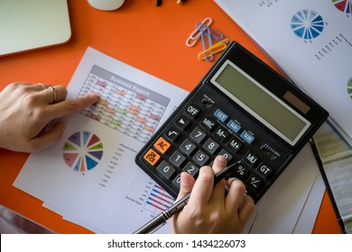 Business woman accounting concept financial in office and using a calculator to calculate the numbers on his desk in a office. Top View