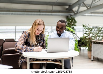 Business woman with African man working on a laptop in the office