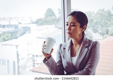 Business woman age 40-50 stands pondered for a solution, a window glass problem that works, with a nervousness on what is going on : Copy space, Soft focus Vintage tone