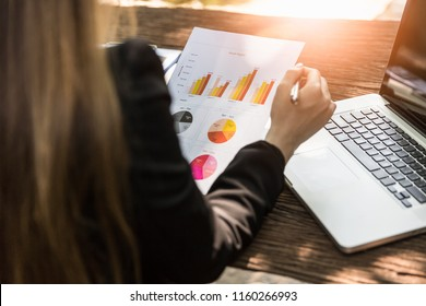 Business woman analysing annual report paper with computer notebook on table