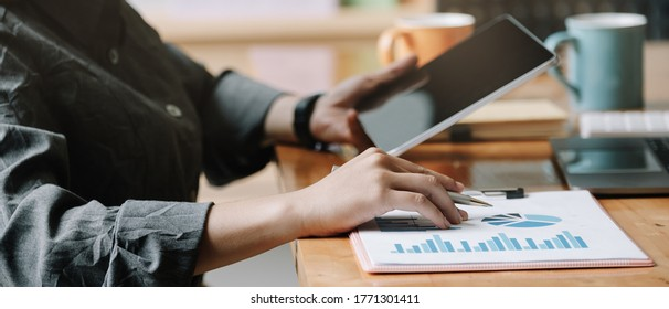 Business woman analysis financial report with tablet computer.