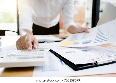 Business woman analysis investment perform data document and calculating a valuation number