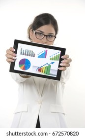 Business woman analyzes graphic data on tablet