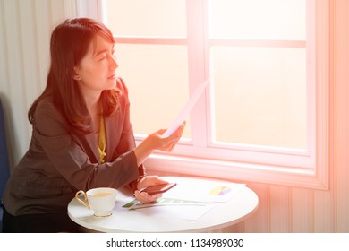 business woman analyzing investment charts with smartphone