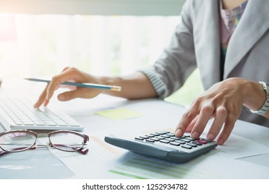 A business woman analyzing investment charts at workplace and using laptop and touch calculator.
