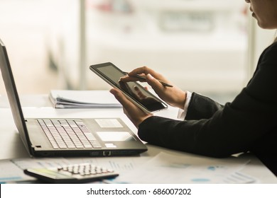 A business woman analyzing investment charts at workplace and using laptop and touch tablet.