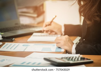 A business woman analyzing investment charts at her workplace and using her laptop ,stock chart, and  writing on notebook, Business concept.