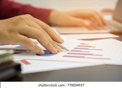 A business woman analyzing investment charts at his workplace and using his laptop ,stock chart , cellphone, close up vintage style.