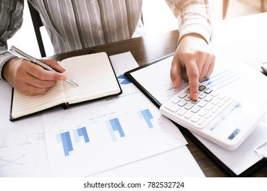 Business woman analyzing investment charts and pressing calculator buttons over documents. Accounting Concept