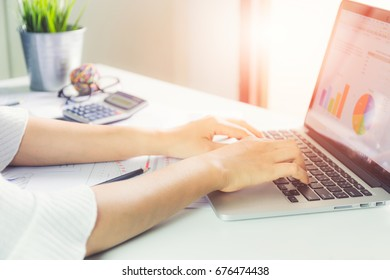 Business woman is analyzing a numerical graph on a laptop in an office.