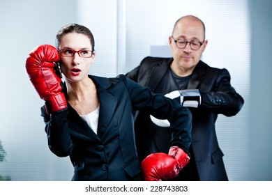 business woman answers the phone during a boxe match with a business man watching his watch impatiently