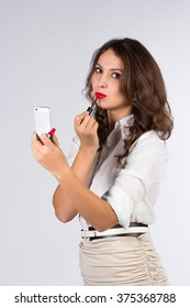 business woman applying lipstick on the work
