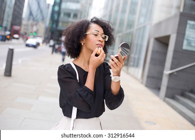 business woman applying lipstick in the street