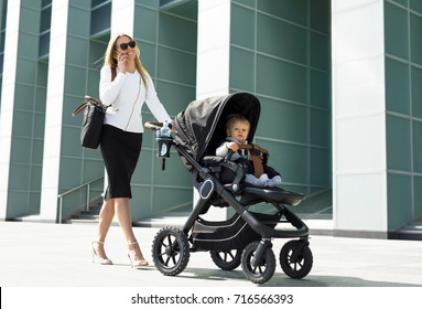 Business woman with baby carriage walking and talking on the phone