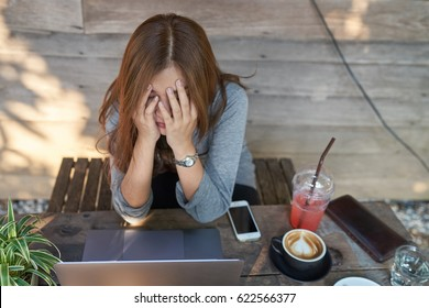 Business woman in bad mood failed and has problem while working with the laptop at cafe. Having headaches.