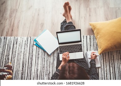 Business woman barefoot dressed pajamas writing notes sitting on living room floor office with laptop, papers and other stuff top view shot.Distance work in worldwide quarantine time concept