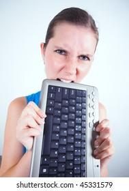 Business woman biting keyboard.
