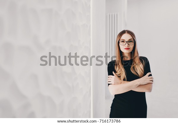 Business woman in black dress looking to the camera in white office with copy space background. Toned.