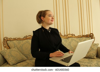 The business woman in black dress is working on the laptop