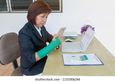 business woman with broken hand sitting and holding green cast  and working on laptop in office, focus on broken hand.