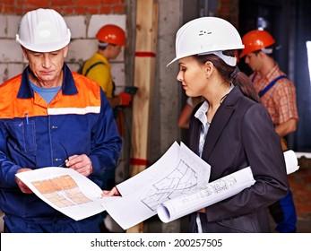 Business woman in builder helmet indoor.