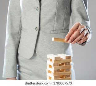 Business woman building tower from wooden blocks. Architecture engineering and construction. Company strategy planning, organization and development. Business motivation concept with wooden jenga game
