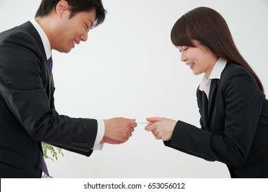 Business woman and businessman exchange business cards