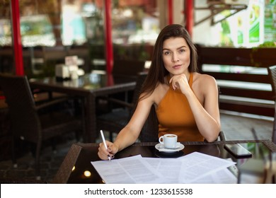 business woman in a cafe fills the documents. Reflections. Work outside the office
