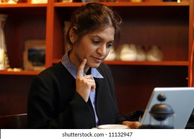 Business woman in a cafe with her finger on her chin