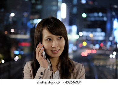 Business woman calling on the phone late at night