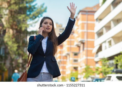 Business woman calling a taxi