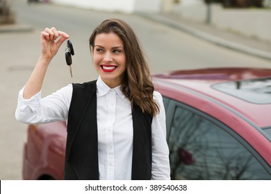 Business woman with car keys standing near her car