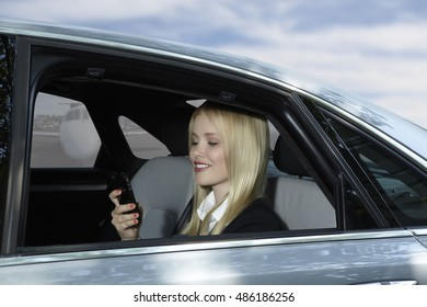 Business Woman in a car talking on her mobile phone with private jet at airport in the background