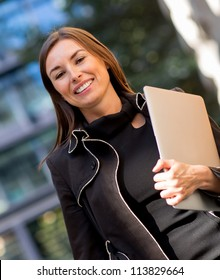 Business woman carrying a laptop out in the city