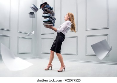 Business woman carrying a pile of papers. Conception of overwork and paper work