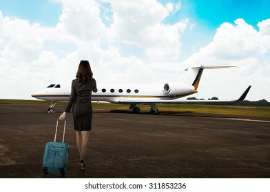 Business woman carrying suitcase to the airplane in the airport