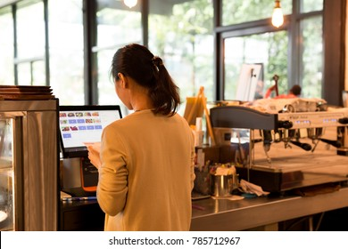 Business woman at the cash register takes orders and bills using modern cash register
