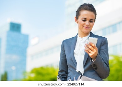 Business woman with cell phone in office district