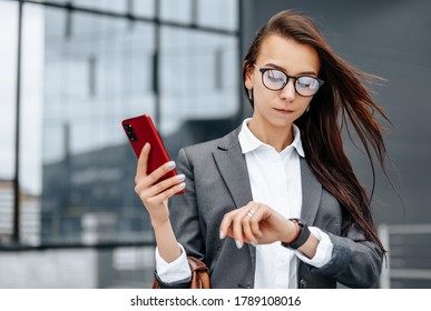 A business woman checks the time in the city during a working day waiting for a meeting. Discipline and timing. An employee goes towards a corporate meeting.