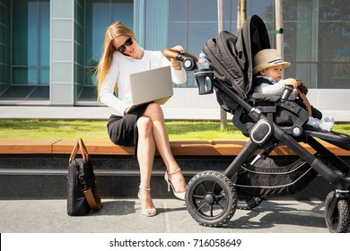 Business woman with child in stroller talking on the phone and working on laptop