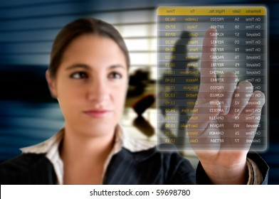Business woman choosing her flight at the airport on a digital futuristic display