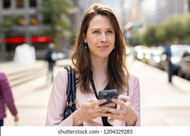 Business woman in city using cell phone walking