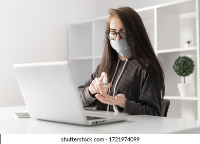 Business woman cleaning her hands with sanitizer gel, wearing protective mask working online on laptop at home office in quarantine due to coronavirus.