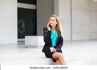 Business woman with coffe and talking on the phone near office