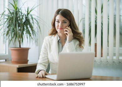 Business woman in company office working on laptop online and communicating remotely