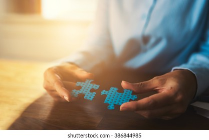 Business woman connecting puzzles, closeup of hands, success concept