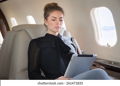 business woman in corporate jet looking at tablet computer