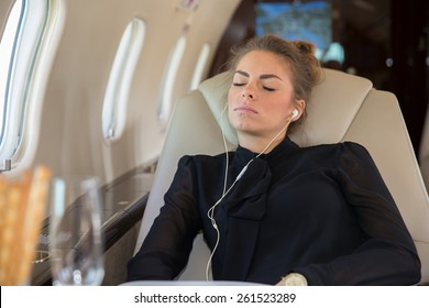 Business woman in a corporate jet relaxing and listening to music