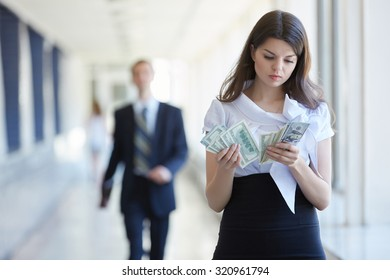 Business woman counts the money, businessman stands with tablet