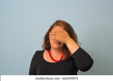 Business woman covers her face with her hands. studio photo on a gray background